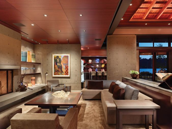 A seating area features several Holly Hunt furnishings, including the New Linden Lounge chair, two Barnard chairs, a Zanzibar table and custom version of her sectional. Chihuly glass lines the shelves of the bar at back.
