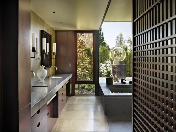 The master bath, which Olson collaborated on with designer Garret Cord Werner, features honed Cambrian black granite countertops with modern, sleek candle sconces. Werner designed the Japanese inspired screen to provide a filter to the walk-in closet.