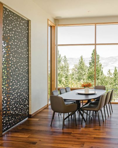 A Minotti Claydon dining table and Flavin chairs outfit the dining room, which captures sweeping mountain views.