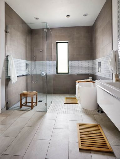 """A guest bathroom was designed initially for the grandparents,"" says Hullinger, ""we created a wet type spa space with grab bars, and all kinds of blocking in the walls. A band of porcelain tile wraps to the tub area."" Vanity by Villeroy Boch - shower and Thasos tub by Aquabrass."