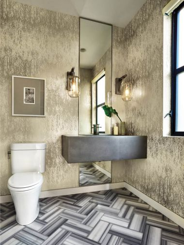 Inspiration for the downstairs powder bath began with the crisp lines of Bianco Striata marble floors in a chevron pattern. The silvery Birches wallpaper is by Schumacher. A floor to ceiling mirror rises behind the cement sink crowned by LBL Lighting sconces.