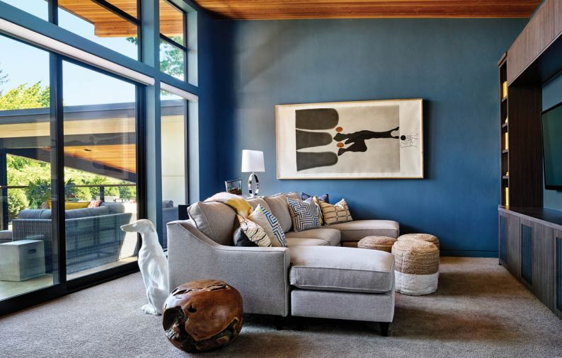 The vertical cedar ceiling in the upstairs family room at right is carried out into the wing-like architecture overhanging the large concrete porch - suitable, says the woman, for hanging out and watching the stars. Rich blue walls and painted baseboards create a warm, enveloping space for cozy family fun. Katyama artwork ties indoors with outside.
