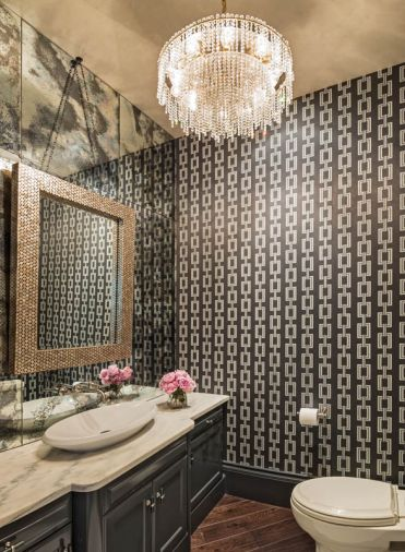 In the guest powder room, the application of tones was reversed from that seen in the living and dining areas with the use of a darker wallpaper and dark cabinetry. Yet Baines maintained a feeling of airiness by hanging a mirror on a wall of mirrors and installing a new counter top.