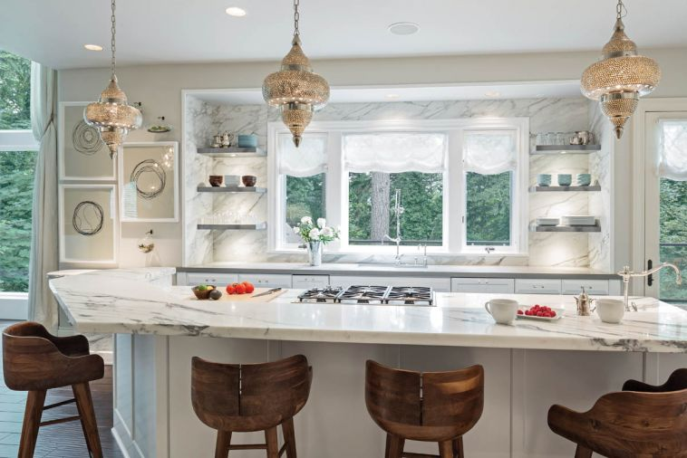 The kitchen was transformed by a refresh rather than a remodel; both the appliances and the footprint were retained by the homeowners. The only structural change introduced by Baines was to remove the upper cabinets that flanked the kitchen window. In their place, a new marble backsplash extends up the wall from the counter to the ceiling.