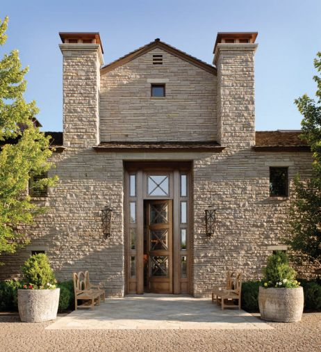 "Four inch cobblestones from Ibison Stone of Oklahoma, which match the stone used in the home's original façade, were placed in a fish scale fan pattern the whole length of the 1/4 mile long driveway. A large fountain was replaced with an exterior ""tile carpet"" that defines the entry. Sevigny built a temporary mezzanine to help finish carpenters and mason John Taylor, who installed the heavy stone fireplace blocks from China. Some of the stones were cut from water troughs in which well-worn rope holes used to tether animals are still visible."