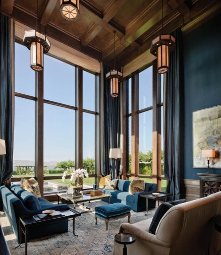 "Blue jewel tones found in the Holly Hunt sateen sofas, India rep fabric walls and silk curtains enliven the living room. Rasar's signature ""Kenny G"" sofa design sits on a Driscoll Robbins flat weave rug. Custom chandeliers camouflage recessed lighting."