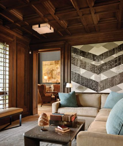 "Richer tones and a darker color palette extend to the coffered walnut ceilings and custom lighting designed to aid the homeowner's sensitivity to light in a bright climate. The inside backs of the wing back chairs in the adjacent living room feature embossed leather. Rasar recommended Romano create large shutters for room-to-room continuity. ""We built them as a door with a louvered shutter inside it and carefully aligned the pieces to coordinate with the rest of the paneling,"" says Romano."