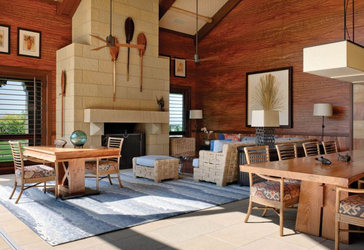 The former garage/utilitarian space is now a beautiful retreat, with precious Koa wood walls and wood-saving wainscot that add drama and warmth. A Himmel sectional pairs with a blue area rug by Hokanson. Table lamp by Gregorius Pineo. Large Douglas fir logs were laid on the ground, and then shaped with a motorized hand planer to resemble the sketches that Rod Knipper provided, before wrapping the ends in hemp rope. Mahogany beams are interrupted by ceiling bamboo mats.