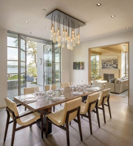 Because of the narrow zoning envelope, the dining room and kitchen are joined together to capitalize on space. A custom Scott Chico Raskey glass chandelier crowns the Holly Hunt table and chairs.