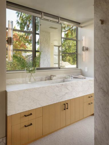 In the master bathroom, Steve Hirt Studio built the tubular sconces. The sliding vanity mirror is by Metal Solutions.