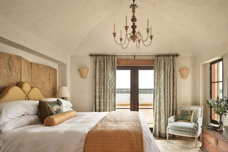 Cast stone sconces in the master add authentic ambiance; headboard and screen design by Hyde Evans.