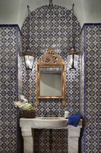 Antique mirror and sconces add shine and light to the powder bathroom's blue and white hand painted tiles by Mosaic House. Industrial Centro faucet from Old and Elegant in Bellevue.