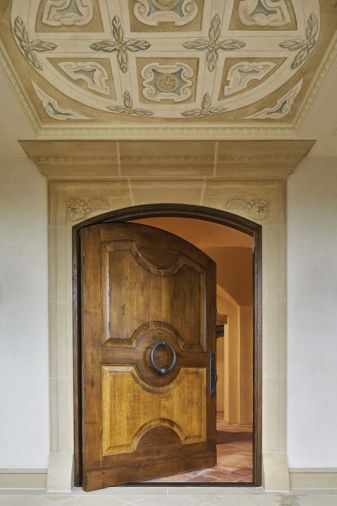 The Great Northwest Door Company crafted the arch oak pivot entry door crowned with a hand painted fresco designed by Hyde Evans Design and executed by Cathy Conner of Studio C.