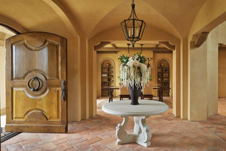 Parefeuille terra cotta tile flooring stretches beyond entry to dining room. To keep with Tuscan home traditions, no baseboards were used.