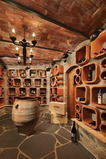 "Chimney flue tiles double as wine bottle storage, adding a whimsical touch to the fan shaped wine cellar.  ""Edifice Construction did a great job with a challenging space,"" says Gelotte, who used piles of mortar to keep the flue tiles in place. A traditional arched ceiling with terra cotta tile and steel beams is topped with concrete."