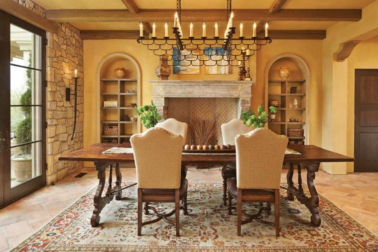 The dining room chandelier was designed by Hyde Evans, based on an antique. Sconce by Woodland Furniture. Antique stone fireplace from Chateau Domingue in Houston.