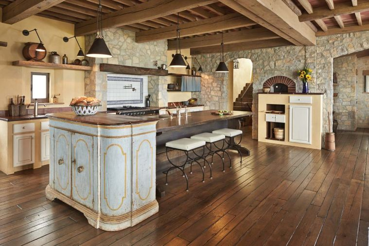 Tuscan architectural methods were challenging for many of the local craftsmen, especially those asked to re-create the appearance of typical late 17th, early 18th century kitchen cabinets that were made from cement or plaster and then fitted with painted wooden doors. The team designed the island to resemble an antique farm table; pendant task lighting designed by Hyde Evans. A very old antique cupboard with original paint abuts the island, mimicking the angle of the wood burning pizza oven set into the rustic stone wall opposite.