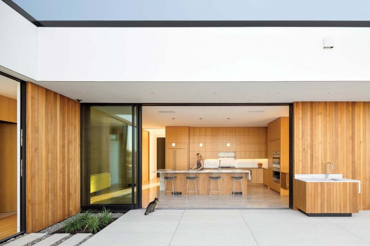 Ash+Ash beautifully achieves one of the core tenants of modern architecture: blurring the boundaries between indoors and outdoors. A paneled sliding glass door allows the wall between the kitchen and pool terrace to be eliminated completely. Exterior cedar cladding in similar tones to the kitchen cabinetry, as well as shared design elements between the main kitchen and outdoor sink and countertop, provide visual links between the interior and exterior of the home. The terrace is paved in locally fabricated, pre-stressed concrete pavers, which are smooth and durable as well as low-emissivity.