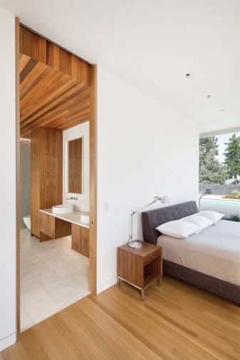 The master bedroom combines textured glass tile on the far wall with wood cladding that extends from the ceiling to the exterior soffit, creating a unique sense of enclosure.
