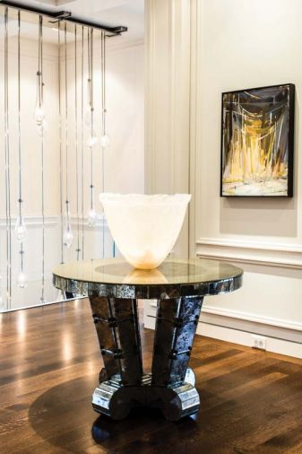 "A Jean de Merry ""Amalfi"" entry table with mercury mirrored glass and bronze accents. Bronze staircase pickets by GCW. Artwork is from the client's collection."