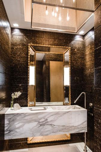 Custom carrara marble vanity and natural stone walls, gilded mirror and chandelier by GCW distinguish the first of two powder rooms