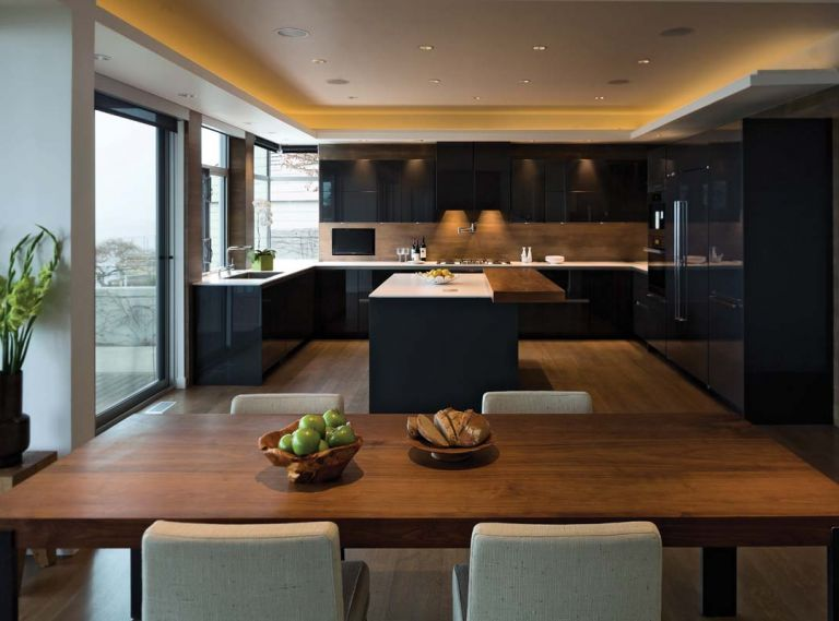 The countertops are made of one-centimeter thick Silestone quartzite. Thin and delicate, the design creates the appearance of a floating white plane, almost weightless, atop a grounding base of graphite grey cabinets. The countertops are sealed with a suede finish to provide a stain-proof, smudge-proof surface. High gloss graphite grey laminate panels are used around the perimeter to clad the fridge, freezer and tall pantry cabinets.