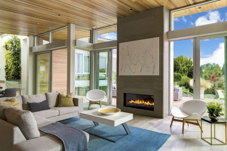 A soaring porcelain Italian tile fireplace parallels custom sliding glass doors leading to the deck. An art lift featuring their child's artwork reveals and hides TV.