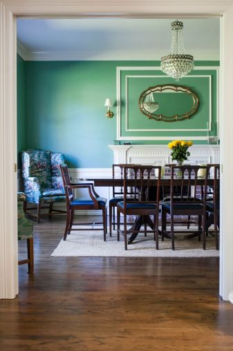The bold green hue in the dining room was chosen from a collection of historic paint colors, yet it feels very contemporary. The Gishes already owned the easy chair and dining set, but they reupholstered the seats in navy leather for a fresh look.