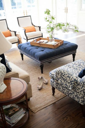 Traditional details like turned wood legs on furniture, a crisp neutral-and-navy color scheme, and preppy, grosgrain-inspired trim on upholstery gives the living room a very classic, comfortable feel.