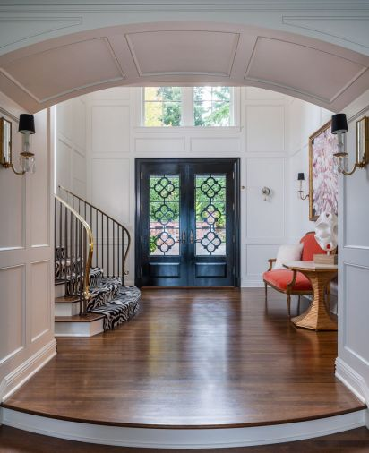 "Brunner designed a series of thematic archways leading from the brick entry to foyer that ""announce"" the newly revealed connection between indoors and out. Custom steel panel adds drama to the NW Door & Sash painted solid mahogany door."