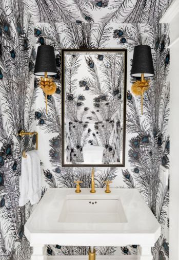 Brass and a vertically patterned peacock wallcovering in black, white and a touch of turquoise enliven a diminutive powder room.