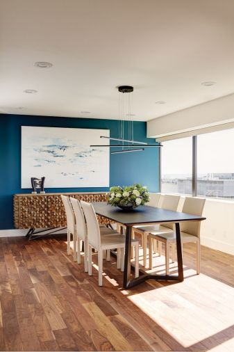 In the kitchen and dining room, chartreuse chairs contrast brightly against a cool-toned dark oak cabinetry. To the left, a red and teal painting by Dale Chihuly provided initial design inspiration, and brings an active, joyful energy to the space. To the right, another white and blue canvas from Mya Kerner echoes the teal color of the accent wall, while a natural wood sideboard from Anthropologie adds dynamic, almost hedgehog-like texture.