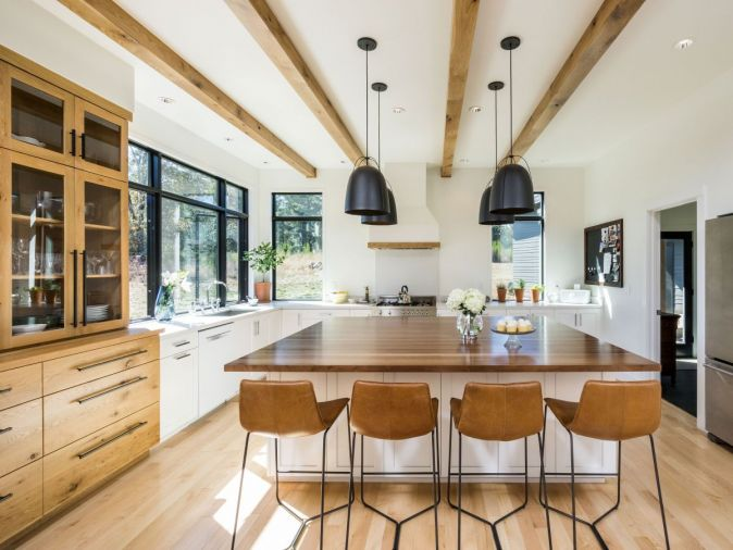 The kitchen artfully blends three different types of wood by balancing multiple textures with clean white walls and an open layout perfect for entertaining. The countertops and backsplash are made from Caesarstone, an engineered quartz that offers easy maintenance and great durability.